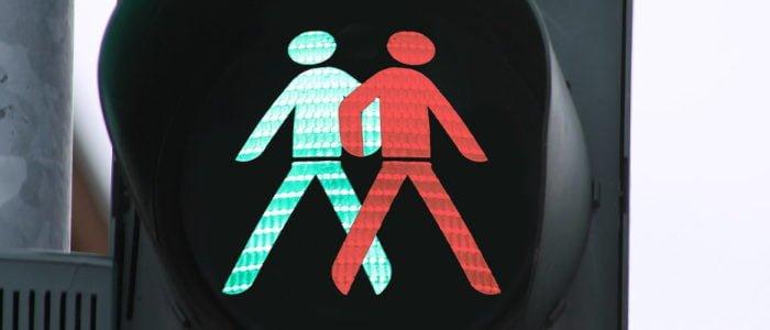 Leuchtende Ampel mit grünem und rotem Ampelmännchen, gehen in unterschiedliche Richtungen